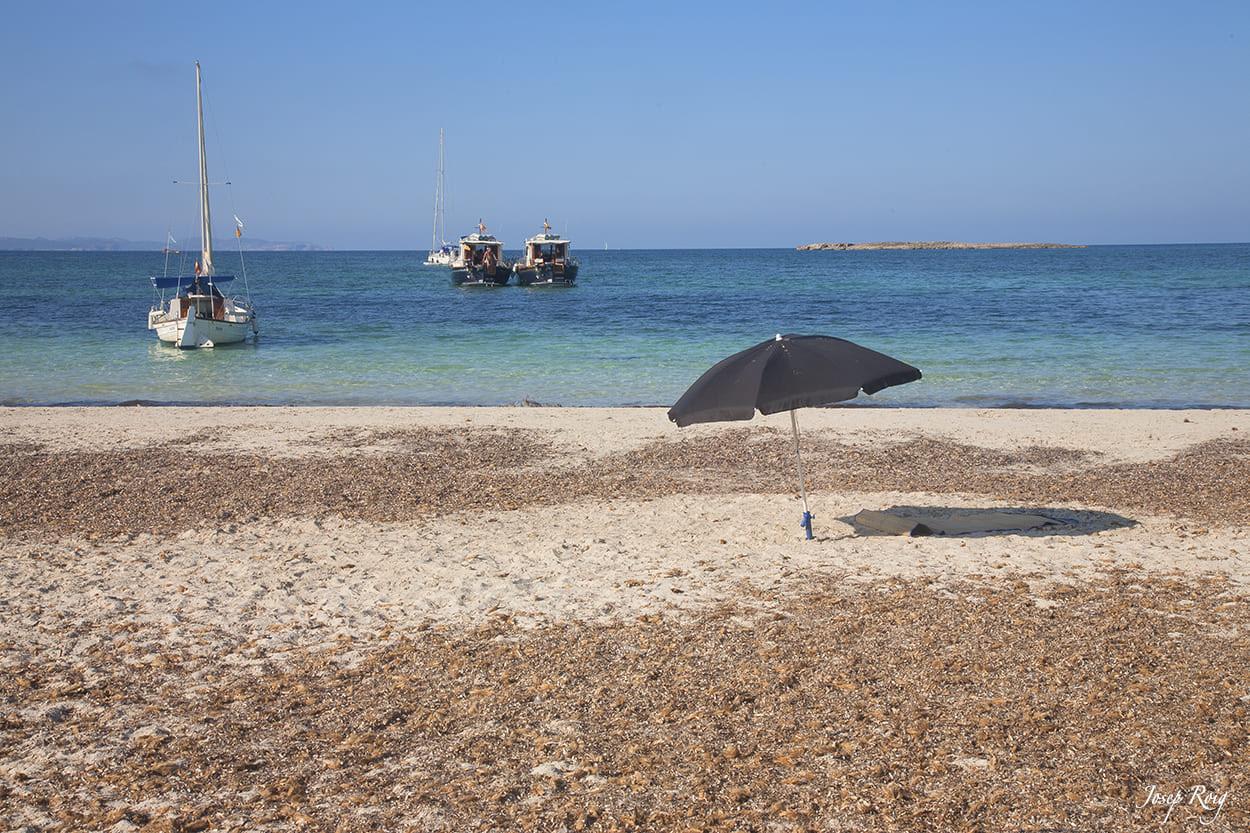 Sonnenschirm und Boote am Strand es carbó, la colonia de sant jordi